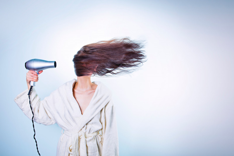 Brunette woman blow drying her hair wearing a dressing gown
