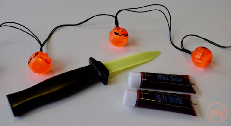 Retractable toy knife and two tubes of fake blood on a white table